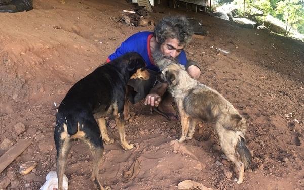 Um morador de rua usa dinheiro de esmola para comprar comida para cachorros