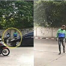 Homem para sua moto para poder ajudar cachorro a atravessar a rua